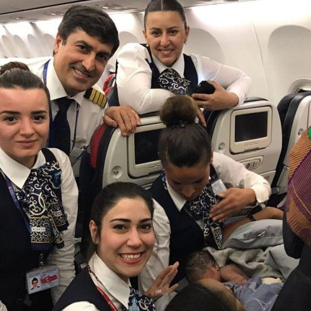 Woman with newborn and cabin crew on flight